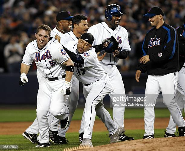 Joyous New York Mets mob grinning third baseman David Wright after Wright hit an RBI walkoff single off New York Yankees' closer Mariano Rivera in...