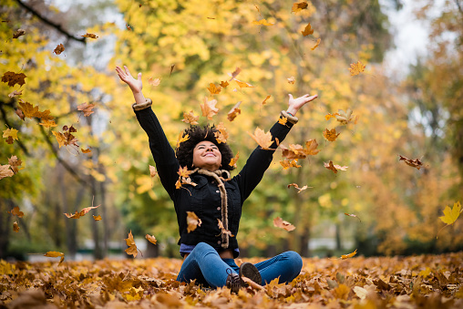 Joyous teen playing with dry maple leaves 1016602340