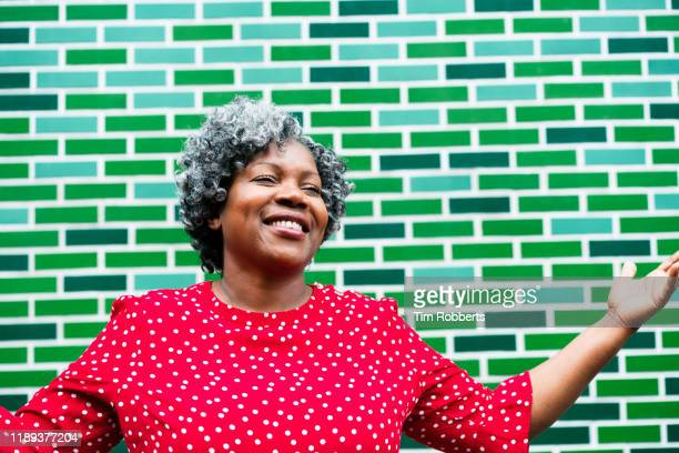 joyous woman infront of green wall - city stock pictures, royalty-free photos & images