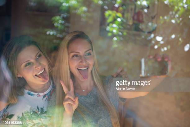 joyous women posing while sticking their tongue out - sneering stock pictures, royalty-free photos & images