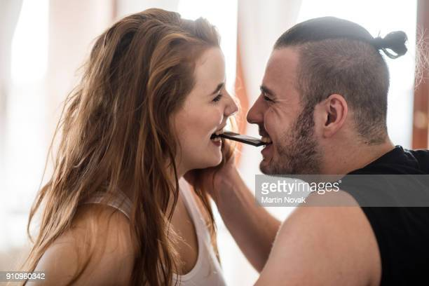 joyous young couple eating chocolate together - couple chocolate stock pictures, royalty-free photos & images