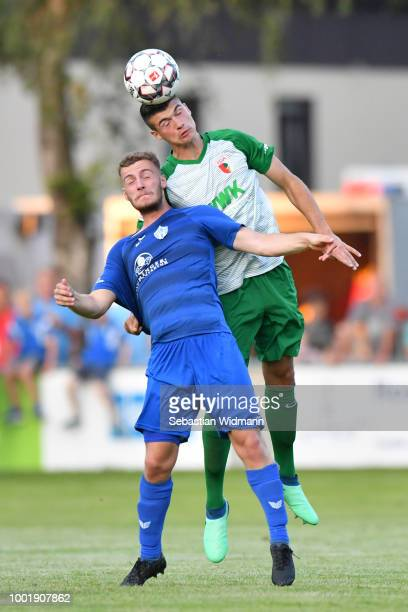 Jozo Stanic of Augsburg and Dominik Amberger of Olching jump for a header during the preseason friendly match between SC Olching and FC Augsburg on...