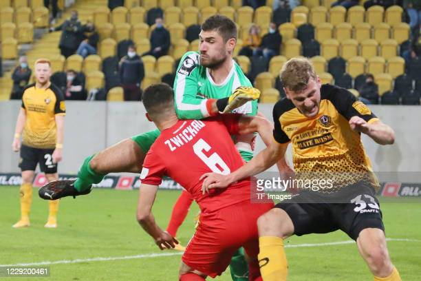 Jozo Stanic of FSV Zwickau and goalkeeper Johannes Brinkies of FSV Zwickau and Christoph Daferner of SG Dynamo Dresden battle for the ball during the...