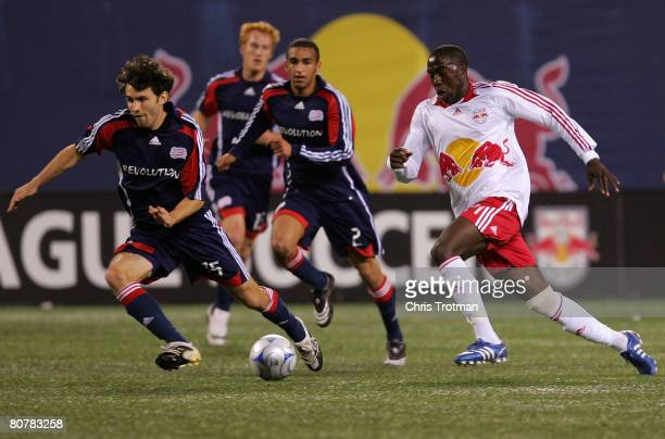 Jozy Altidore of the New York Red Bulls pushes the ball up field against Michael Parkhurst and Amaechi Igwe#2 of the New England Revolution at Giants...