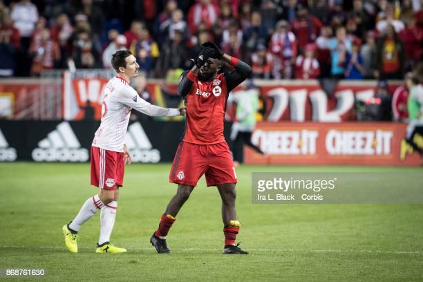 Jozy Altidore of Toronto FC gets pushed off the field by Sacha Kljestan of New York Red Bulls after he is subbed out during the Audi MLS Cup Playoff...
