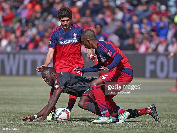 Jozy Altidore of Toronto FC hits the ground under pressure from Adailton and Chris Ritter of Chicago Fire during an MLS match at Toyota Park on April...
