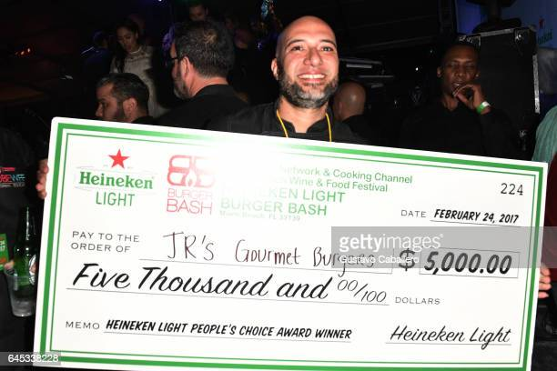 Jr De La Torre from Jr's Gourmet Burgers poses for a photo with his winnings at Heineken Light Burger Bash Presented by Schweid Sons Hosted by...