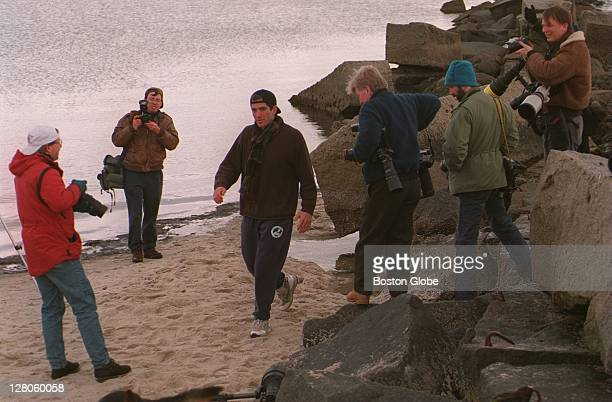 JFK Jr walks along the beach in front of the Kennedy compound surrounded by photographers after his grandmother passed away