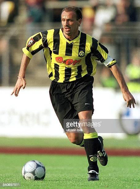 Jürgen Kohler Abwehrspieler beim FußballBundesligisten Borussia Dortmund führt den Ball Er trägt die Kapitänsbinde