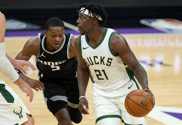Jrue Holiday of the Milwaukee Bucks dribbles around a screen set on De'Aaron Fox of the Sacramento Kings during the second half of an NBA basketball...