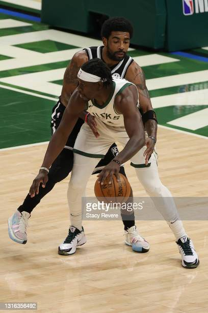 Jrue Holiday of the Milwaukee Bucks is defended by Kyrie Irving of the Brooklyn Nets during the first half of a game at Fiserv Forum on May 04, 2021...