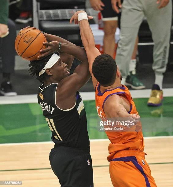 Jrue Holiday of the Milwaukee Bucks shoots against Devin Booker of the Phoenix Suns at Fiserv Forum on July 20, 2021 in Milwaukee, Wisconsin. The...