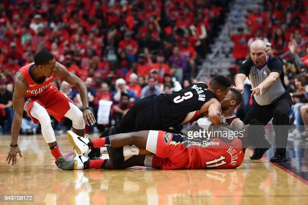 Jrue Holiday of the New Orleans Pelicans and CJ McCollum of the Portland Trail Blazers grab a loose ball during the first half of Game Four of the...