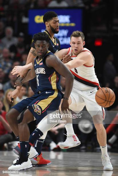 Jrue Holiday of the New Orleans Pelicans and Pat Connaughton of the Portland Trail Blazers go after a ball as Anthony Davis of the New Orleans...