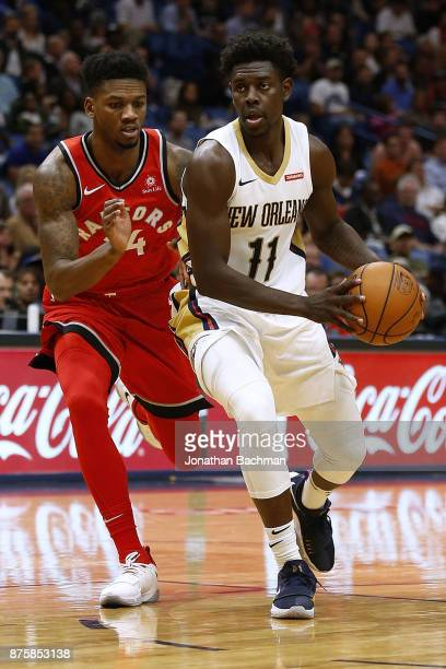 Jrue Holiday of the New Orleans Pelicans drives against Alfonzo McKinnie of the Toronto Raptors during the first half of a game at the Smoothie King...