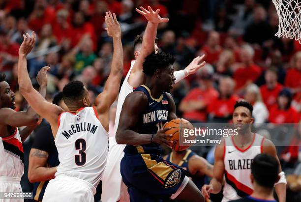 Jrue Holiday of the New Orleans Pelicans drives against CJ McCollum and Jusuf Nurkic of the Portland Trail Blazers during Game One of the Western...