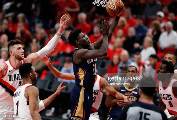 Jrue Holiday of the New Orleans Pelicans drives against Ed Turner and Jusuf Nurkic of the Portland Trail Blazers during Game One of the Western...