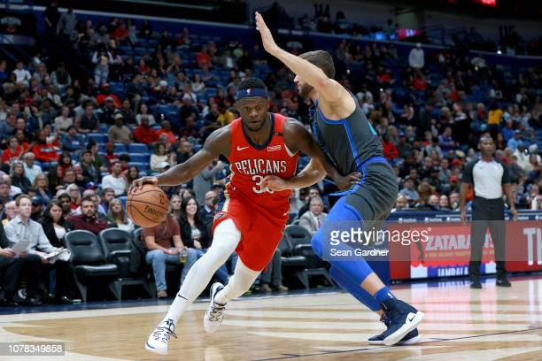 Jrue Holiday of the New Orleans Pelicans drives the ball past Luka Doncic of the Dallas Mavericks during a NBA game at the Smoothie King Center on...