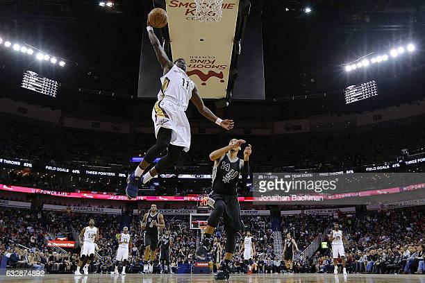 Jrue Holiday of the New Orleans Pelicans dunks past Danny Green of the San Antonio Spurs during the second half of a game at the Smoothie King Center...