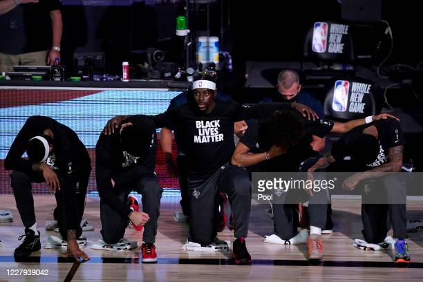 Jrue Holiday of the New Orleans Pelicans looks up while kneeling with teammates in honor of the Black Lives Matter movement during the playing of the...