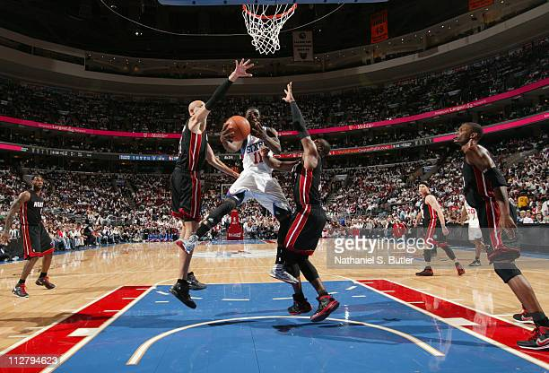 Jrue Holiday of the Philadelphia 76ers shoots against Zydrunas Ilgauskas and Dwyane Wade of the Miami Heat in Game Three of the Eastern Conference...