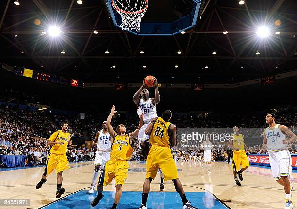 Jrue Holiday of the UCLA Bruins scores a basket against Theo Robertson and Jerome Randle of the University of California Golden Bears during the...