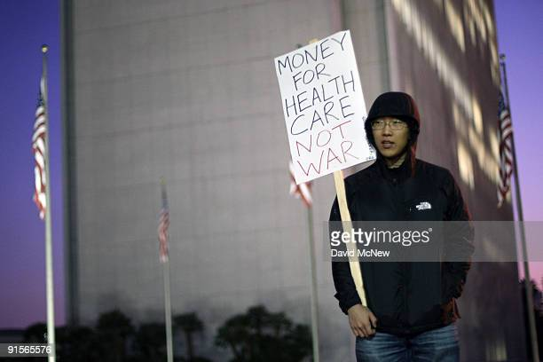 Ju Kim joins antiwar demonstrators in calling for a troop pullout in Afghanistan as they rally near the Federal Building behind Kim eight years after...