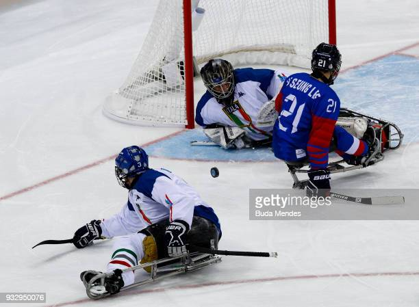 Ju Seung Lee of Korea battles for the puck with goalkeeper Santino Stillitanoof Italy in the Ice Hockey bronze medal game between Korea and Italy...