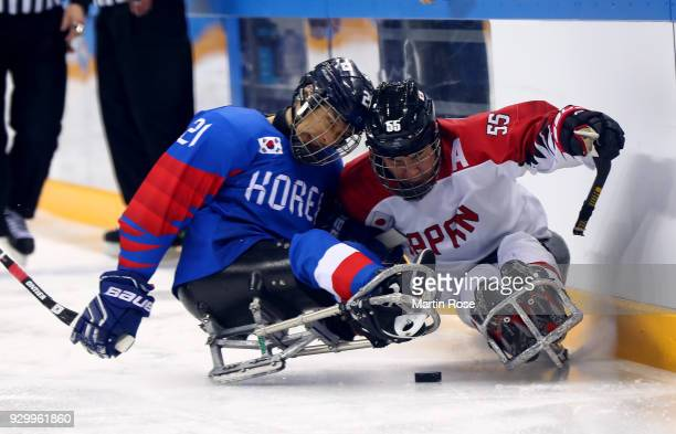 Ju Seung Lee of Korea battles for the puck with Kazuhiro Takahashi of Japan in the Ice Hockey Preliminary Round Group B game between South Korea and...