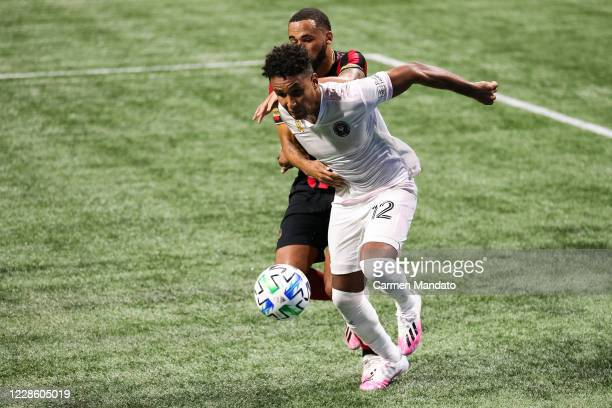 Juan Agudelo of Inter Miami battles for ball control against Anton Walkes of Atlanta United during the second half of a game at Mercedes-Benz Stadium...