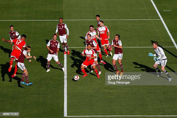 Juan Agudelo of New England Revolution bounces a head ball wide past goalkeeper Clint Irwin of Colorado Rapids as Jared Watts of Colorado Rapids...