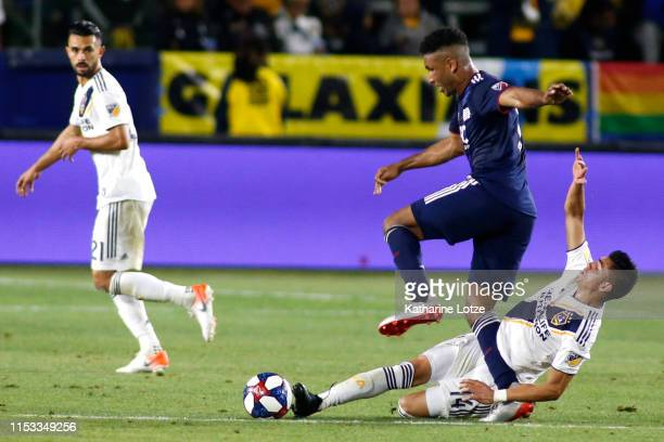 Juan Agudelo of New England Revolution steps over a slide tackle by Joe Corona of Los Angeles Galaxy during the second half of a game at Dignity...