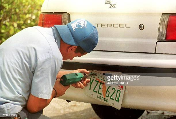 Juan Alberto a mechanic at Alamo Car rental removes an old license plate 07 April 1993 that begins with a Y and reads Lease at the bottom to replace...