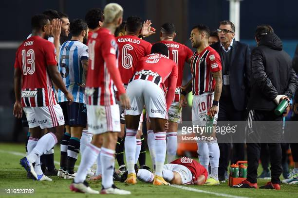 Juan Antonio Pizzi head coach of Racing Club and Dani Alves of Sao Paulo react as Martín Benítez of Sao Paulo lies on the pitch after suffering and...