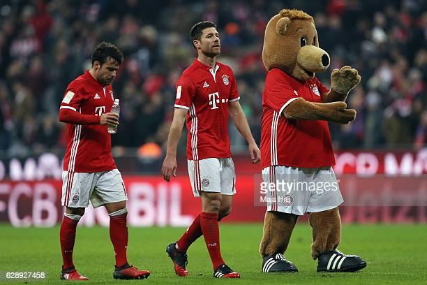 Juan Bernat and Xabi Alonso of Muenchen celebrate with mascot Bernie after the Bundesliga match between Bayern Muenchen and VfL Wolfsburg at Allianz...