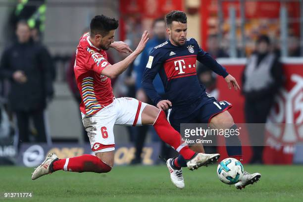Juan Bernat of Bayern Muenchen fights for the ball with Danny Latza of Mainz during the Bundesliga match between 1 FSV Mainz 05 and FC Bayern...