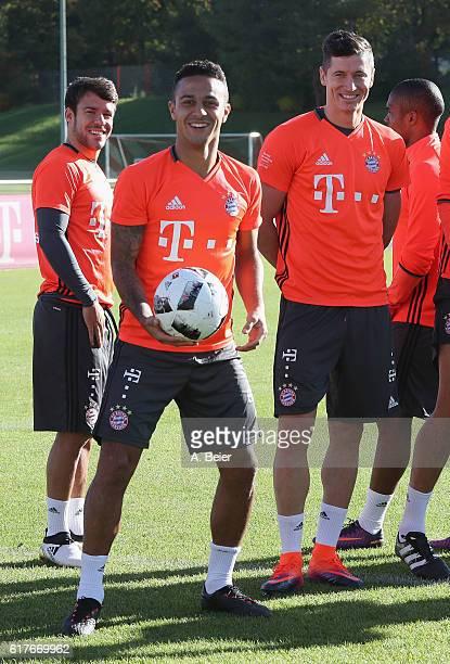 Juan Bernat Thiago Robert Lewandowski and Douglas Costa of FC Bayern Muenchen smile during a training session at the club's Saebener Strasse training...