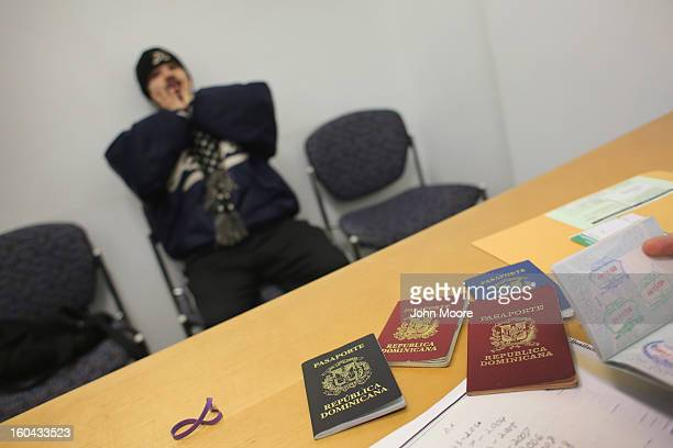 Juan Bonifacio waits as an immigration attorney Andres Lemons sorts through his passports from the Dominican Republic while working on his...