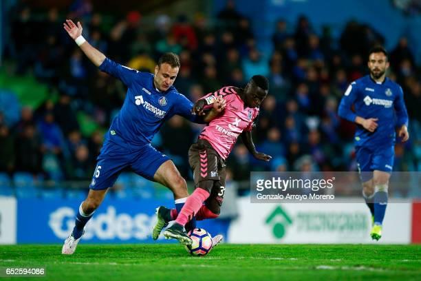 Juan Cala of Getafe CF tackles Amath Ndiaye Diedhiou of CD Tenerife during the La Liga second league match between Getafe CF and CD Tenerife at...