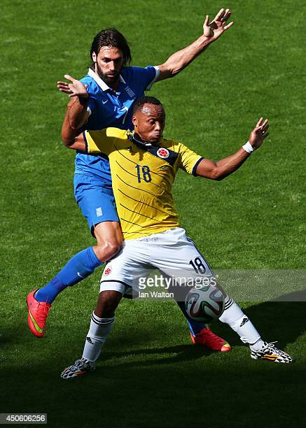 Juan Camilo Zuniga of Colombia holds off a challenge by Giorgos Samaras of Greece during the 2014 FIFA World Cup Brazil Group C match between...
