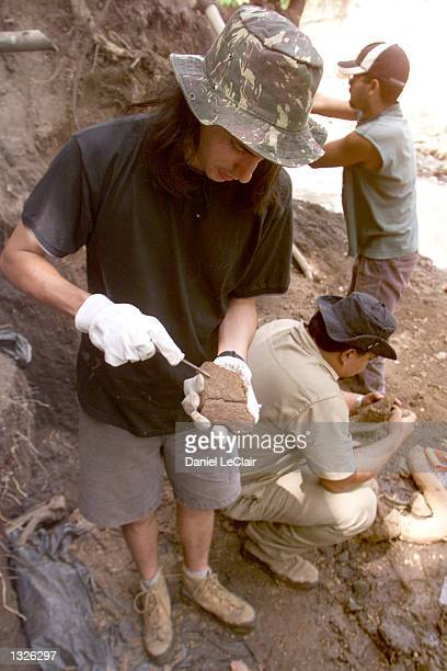 Juan Carlos Cisneros left cleans the shell of a giant armadillo June 25 20001 at the Tomayate River project in Apopa El Salvador The site was...