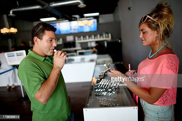 Juan Carlos Fernandez and Chloe Lamb shop for an E liquid flavor for their electronic cigarettes at the Vapor Shark store on September 6 2013 in...