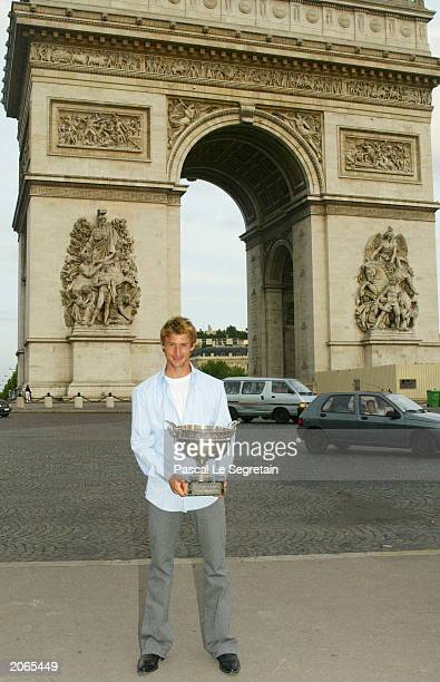 Juan Carlos Ferrero of Spain poses with the trophy with the Arc de Triomphe in the backgroung after winning his mens final match against Martin...