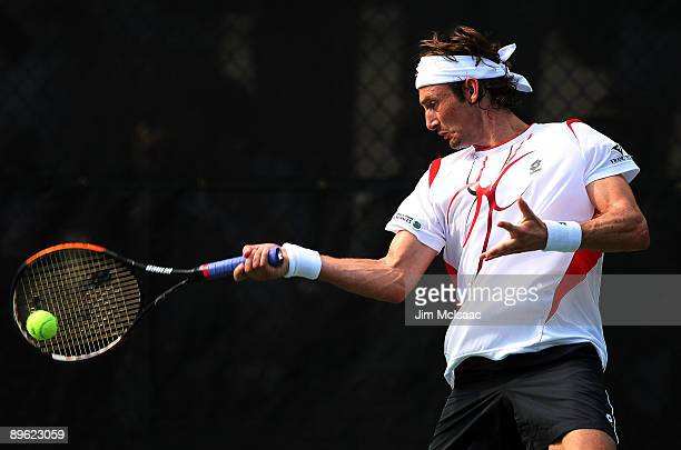 Juan Carlos Ferrero of Spain returns a shot against Tommy Robredo of Spain during Day 3 of the Legg Mason Tennis Classic at the William H.G....