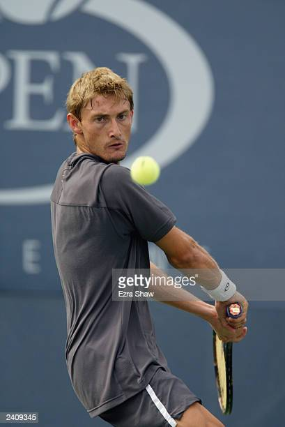 Juan Carlos Ferrero of Spain returns a shot to Gaston Etlis of Argentina during the US Open August 30 2002 at the USTA National Tennis Center in...