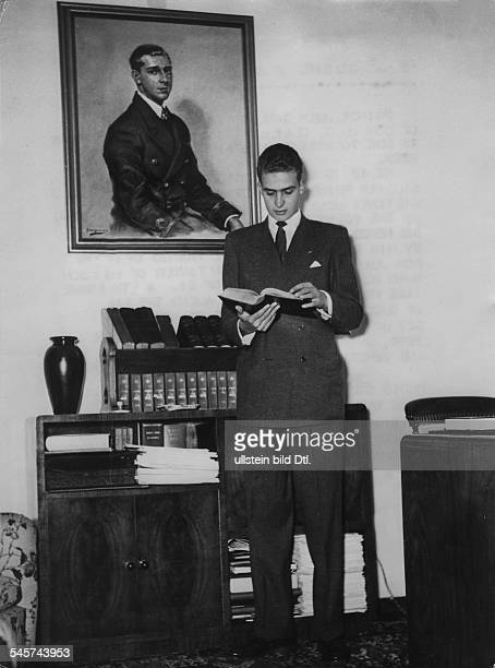 Juan Carlos I *König von Spanien als Kronprinz in seinem Heim in Portugal steht neben einem Porträt seines Vaters Don Juan 1955