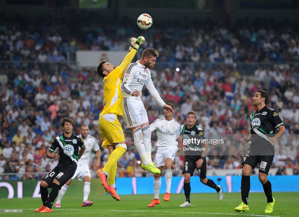 Juan Carlos of Cordoba CF gets his fists to the ball ahead of Sergio Ramos of Real Madrid CF during the La liga match between Real Madrid CF and Cordoba CF at Estadio Santiago Bernabeu on August 25, 2014 in Madrid, Spain.
