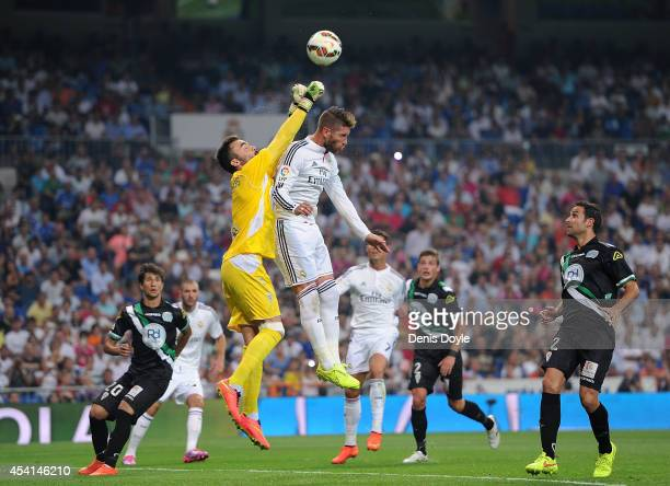 Juan Carlos of Cordoba CF gets his fists to the ball ahead of Sergio Ramos of Real Madrid CF during the La liga match between Real Madrid CF and...