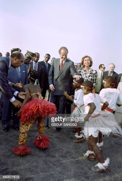 Juan Carlos of Spain and Queen Sofia of Spain are greeted on December 4 1995 by traditional dancers in the Ivorian capital Yamoussoukro where the...