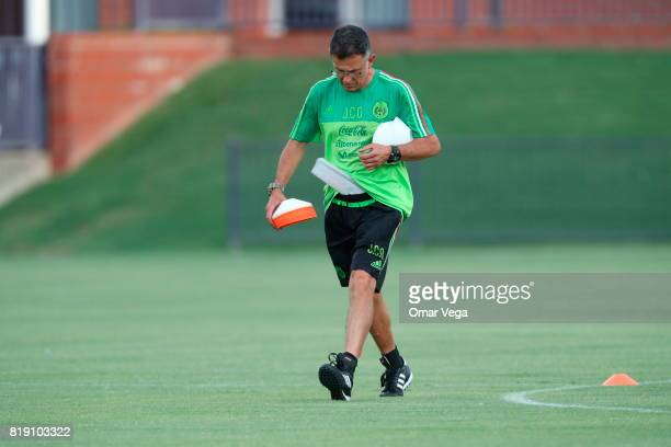 Juan Carlos Osorio coach of Mexico holds cones while walking on the field during the Mexico National Team training session ahead it's match against...